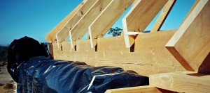 Roof framing above a straw bale wall